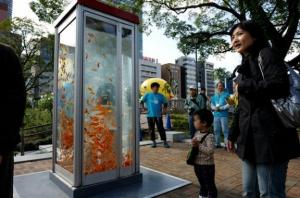 Artistas crean peceras en teléfonos públicos