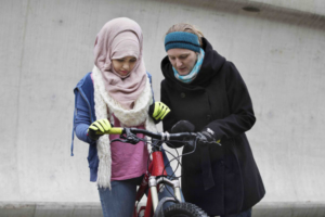 Friends on bikes. Cycling lessons for refugees.